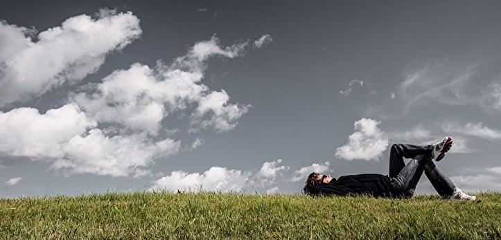 芝生の上で眠っている男性