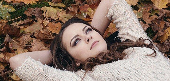 落ち葉の上に横たわる女性