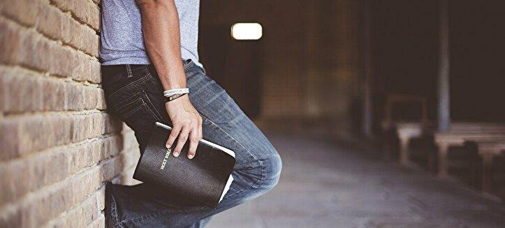 本を片手にたたずむ男性
